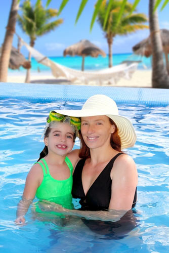 Mother and daughter in pool with palm trees in background
