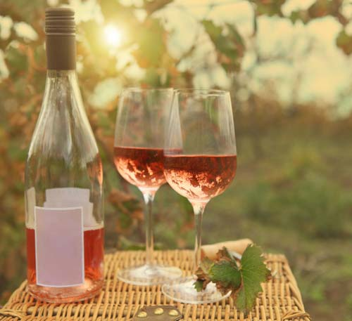 Bottle of wine and two glasses on top of picnic basket