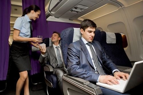Businessman on plane working on computer