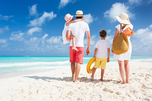 Mother and father walking their two children on a white sandy beach