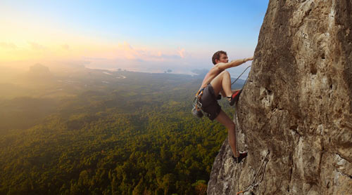 man free climbing a mountain rock face