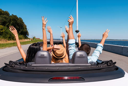 people riding in a convertible car with arms raised