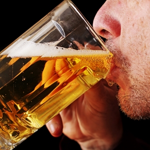man drinking from a beer glass