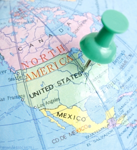 A section of a globe of North America with a green stick pin in the center of the United States