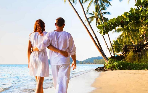 two honeymooners walking along the beach