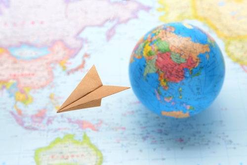 A globe sitting on a map behind a paper airplane