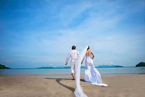 two newlyweds walking along the beach