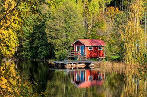 red cabin on a lakeside in the forest