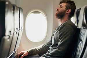 man with closed eyes in airline seat