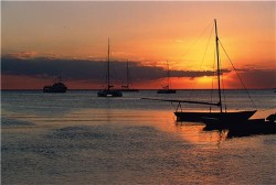 sail boats anchored in bay at sunset