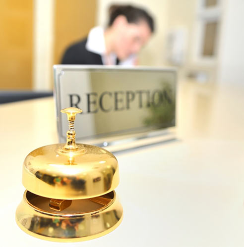 Gold bell at reception desk in hotel